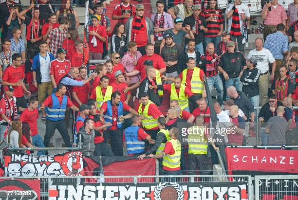 Security guards seperate supporters of Ingolstadt and skinheads fighting in the sector during the Second Bundesliga match between FC Ingolstadt and...