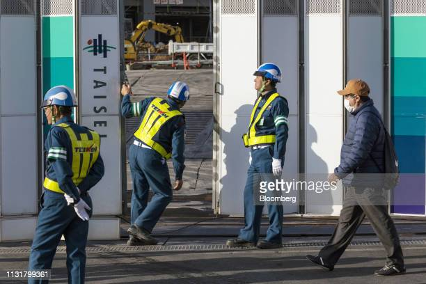 Security guards stand at an entrance gate to the construction site of the New National Stadium a venue for 2020 Summer Olympics and Paralympics...