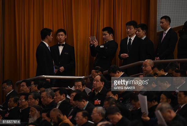 Security guards stand behind delegates and guests during the third plenary session of the National People's Congress at the Great Hall of the People...