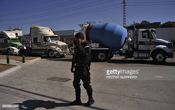 Security guards stand guard at a Pemex distribution center which is blockaded by truckers protesting the rise in fuel prices in Guadalajara Jalisco...