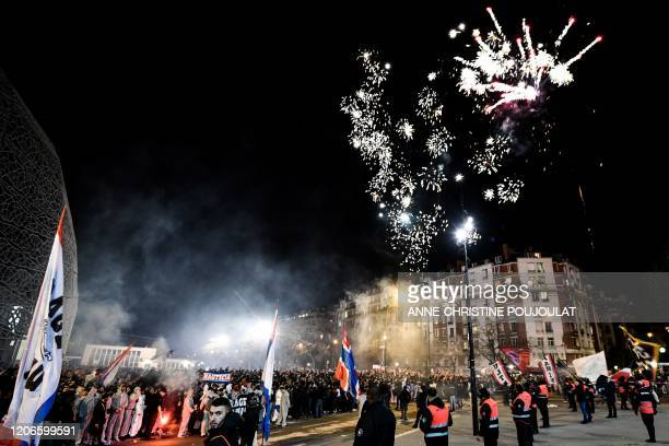 Security guards stand in front of PSG's supporters waving flags of the team as fireworks explode in the sky outside the Parc des Princes stadium...