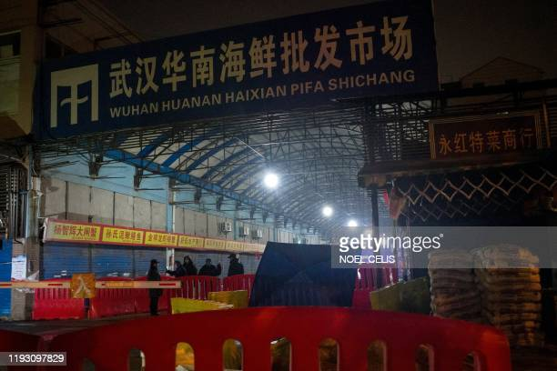 Security guards stand in front of the closed Huanan Seafood Wholesale Market in the city of Wuhan in the Hubei Province on January 11 where the Wuhan...