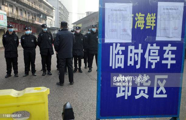 Security guards stand in front of the closed Huanan wholesale seafood market where health authorities say a man who died from a respiratory illness...