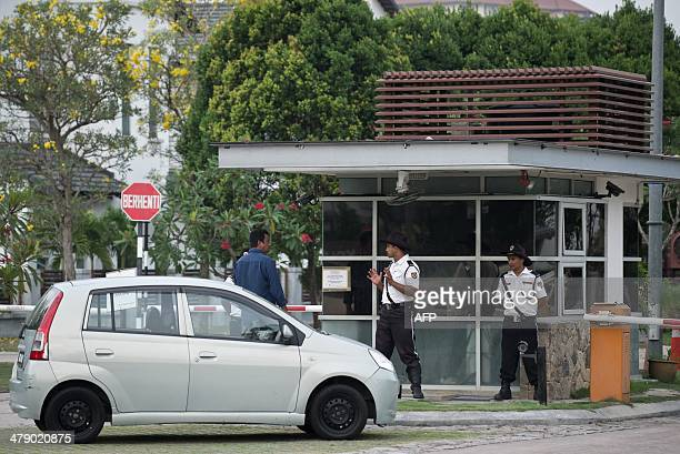 Security guards stand in front of the main gate house of the area where captain Zahari Ahmad Shah lives the pilot captain of the missing Malaysia...