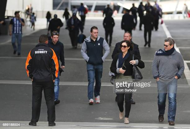 Security guards stand on patrol as football fans walk from Southern Cross Station to the ground during the round 10 AFL match between the Carlton...
