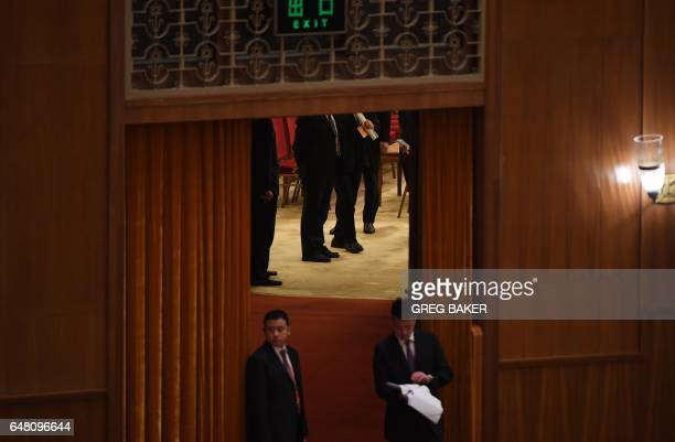 Security guards stand outside a room used by officials after the opening session of the National People's Congress China's legislature in the Great...