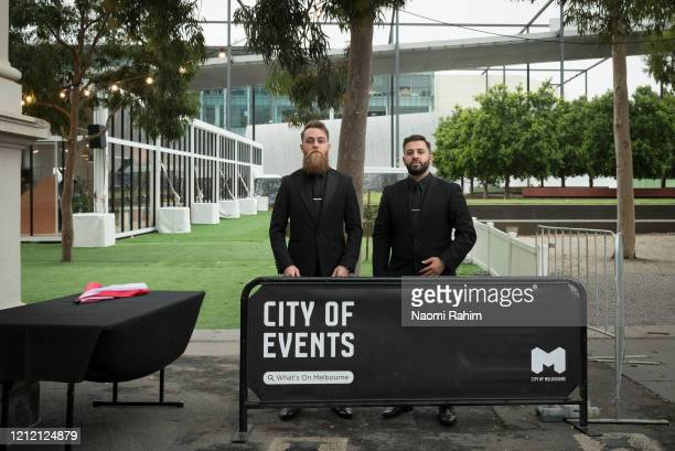 Security guards stand outside an empty plaza on March 13 2020 in Melbourne Australia Melbourne Fashion Festival organisers announced on Friday...