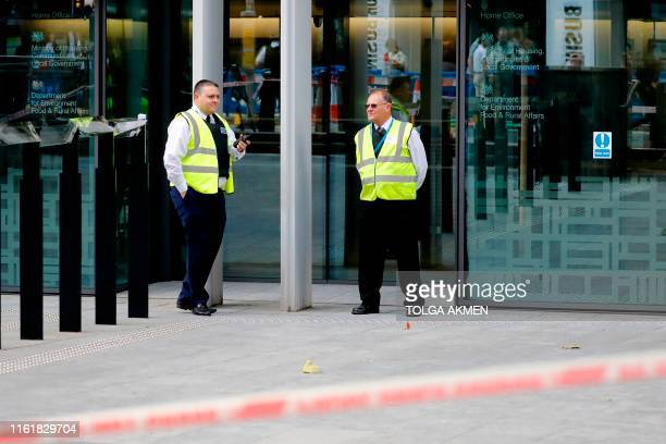 Security guards stand outside the entrance to Britain's Home Office in central London on August 15 following a stabbing incident A man was taken to...