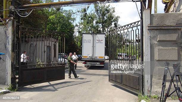 Security guards stand outside the Malyshev military tank and armored vehicle factory after the train carrying of 282 of the 298 people on the downed...