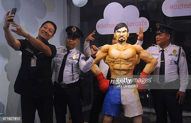Security guards take a selfie with a life size 70 kilogram cake worth 4000 USD of Philippine boxing icon Manny Pacquiao at a cafe in Manila on May 2...
