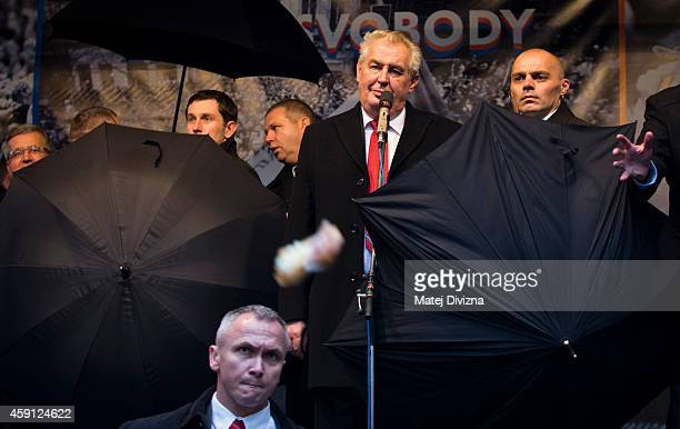 Security guards try to shield President of Czech Republic Milos Zeman with umbrellas as people throw eggs and tomatoes during the unveiling of a...
