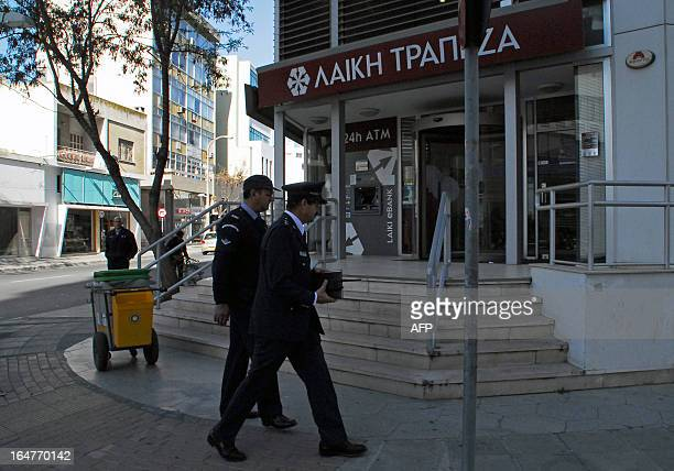 Security guards walk outside a Laiki bank branch in the centre of the Cypriot capital Nicosia on March 28 ahead of their reopening after an...