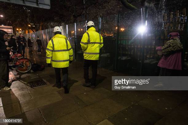 Security guards walk past protestors on February 4, 2021 in London, England. Earlier this week a High Court Judge told HS2's national eviction team...