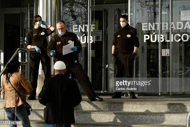 Security guards wear a protective face mask at the Trial Court on March 13, 2020 in Madrid, Spain. Today known cases of Covid-19 in Madrid are 2 this...