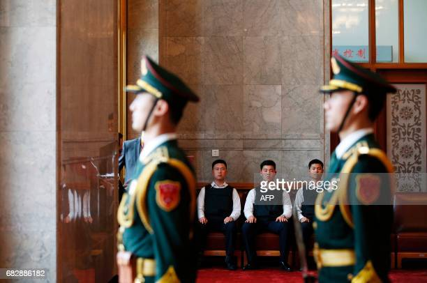 Security guards wearing bulletproof vests sit at the Great Hall of the People before the meeting between Russian President Vladimir Putin and Chinese...