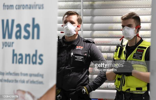 Security guards wearing face masks wait to greet arriving passengers at the Airport in Vantaa Finland on March 27 2020 A large number of Finnish...