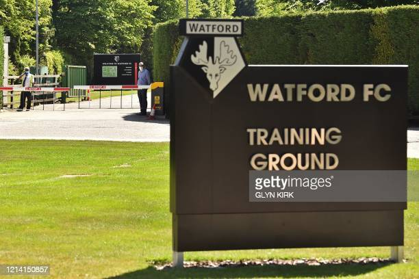 Security guards wearing PPE man a gate at Watford's training facility at London Colney in north London on May 20 2020 as training continues for...