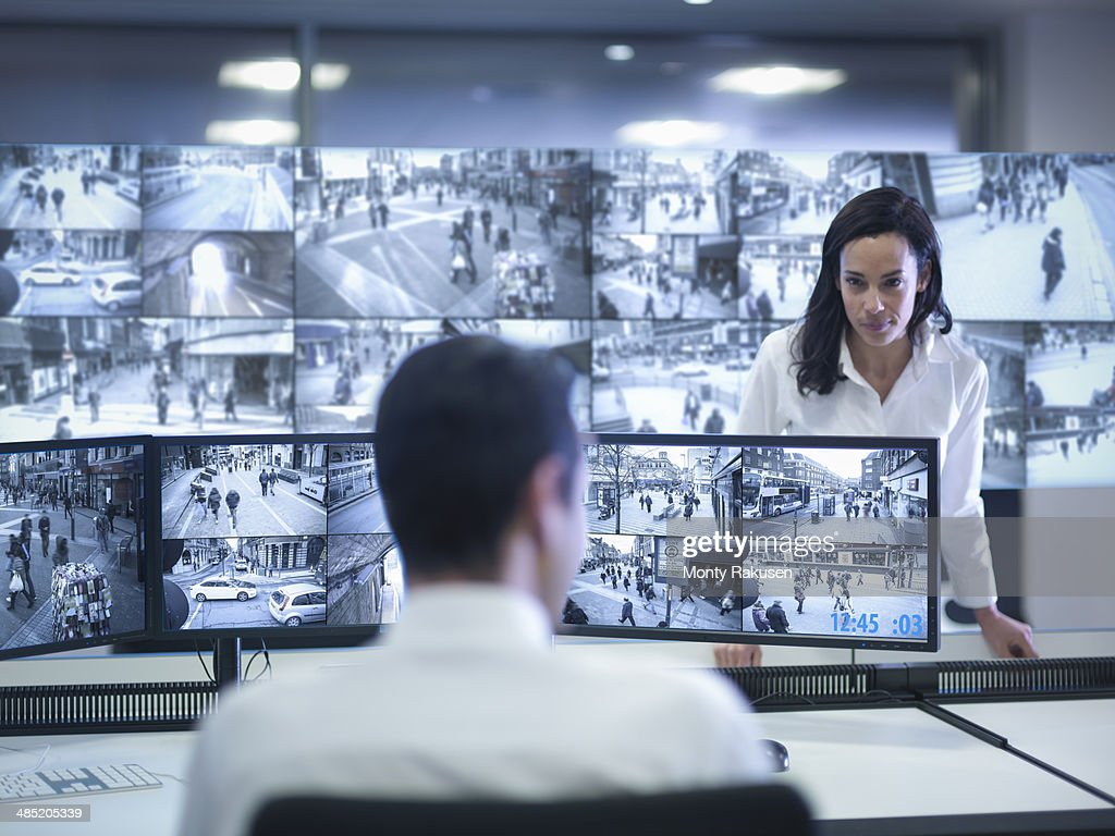 Security guards working at CCTV screens in control room : Stock Photo