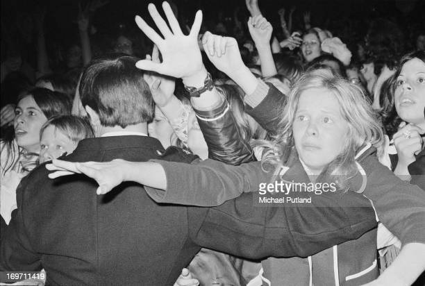 A security holds back part of the crowd during a concert by English glam rock group TRex on their fourdate British tour June 1972