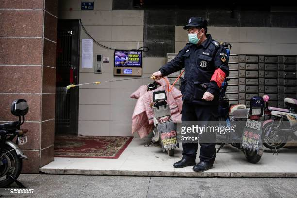 A security is using alcohol to disinfect in community on January 23 2020 in Wuhan China Flights trains and public transport including buses subway...
