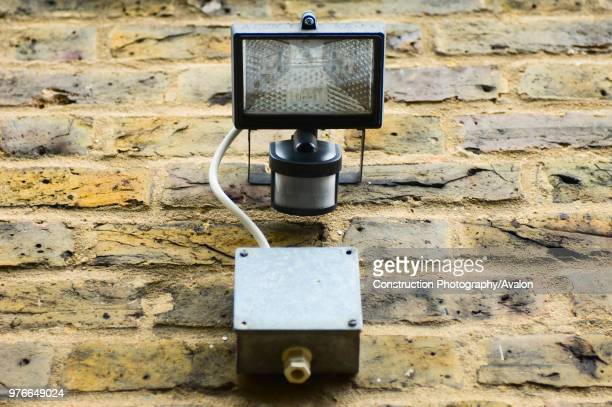 Security light and movement sensor fixed to wall of house