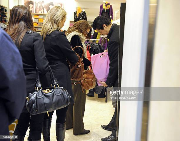 A security man checks the bags of a shopper on December 17 2008 in a shop close to Le Printemps one of Paris's top department stores a day after an...