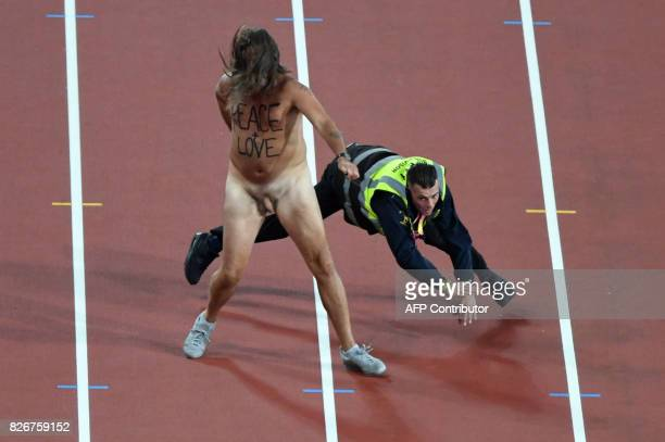 Security man falls as he tries to stop a streaker running along the track before the final of the men's 100m athletics event at the 2017 IAAF World...