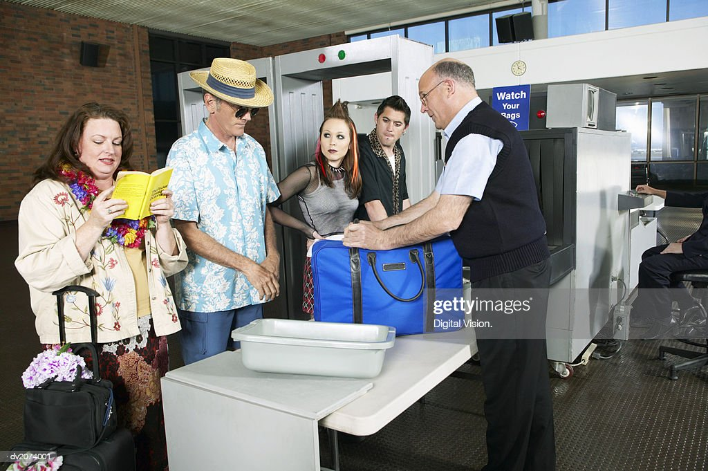 Security Man Looking Examining a Man's Luggage at an Airport X Ray Machine : Stock Photo