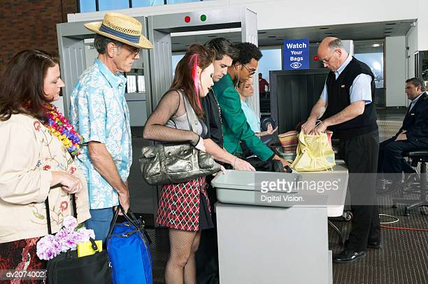 Security Man Looking Examining Luggage by an Airport X Ray Machine