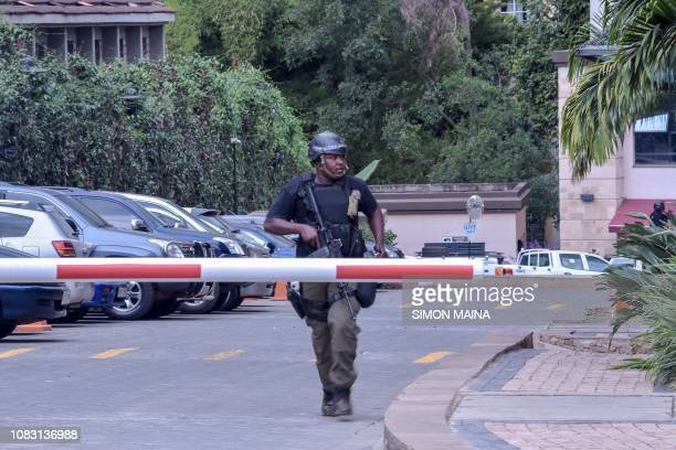 A security man runs into safety in the scene of an explosion at a hotel complex in Nairobi on January 15 2019 A blast at the DusitD2 compound which...