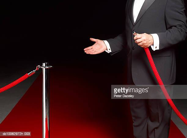 security man showing way past rope on to red carpet, mid section - roped off stock photos and pictures