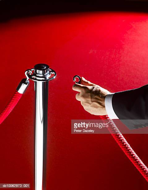 security man unclipping rope, close-up of hand - doorman stock photos and pictures