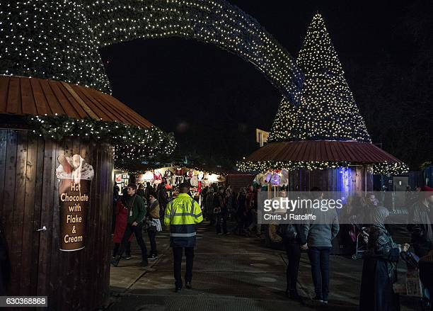 A security marshal walks amongst Christmas stalls and past a couple holding hands at the Winter Wonderland in Hyde Park on December 21 2016 in London...