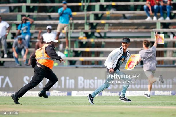 Security marshals chases streakers as he invades the field of play on the fourth day of the fourth Test cricket match between South Africa and...