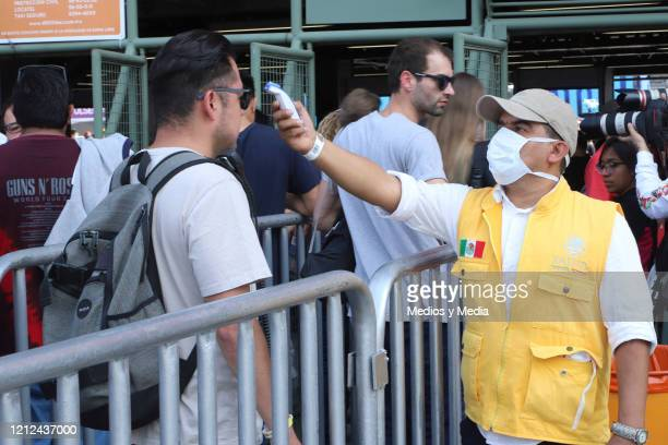 Security member checks the temperature of a fan, as a preventive measure against the coronavirus outbreak at the entrance to the Vive Latino 2020 at...