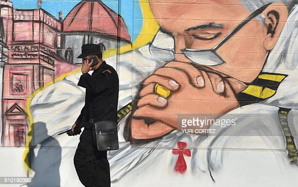 A security member speaks on his mobile phone next to a mural painting depicting Pope Francis in Ecatepec a rough crimeplagued Mexico City suburb...