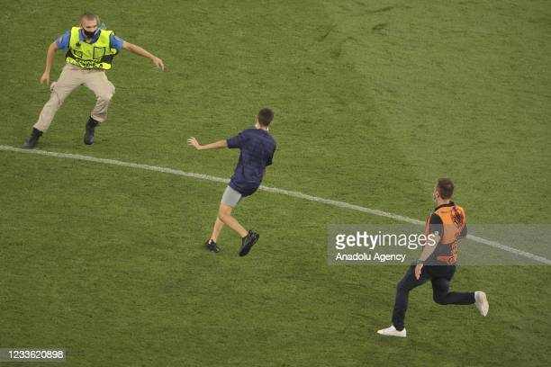 Security members intervene to block a fan who entered the field at the end of the EURO 2020 Group F match between Portugal and France at Ferenc...