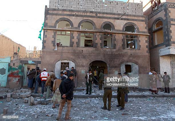 Security members of the Shiite Huthi movement and emergency personnel gather outside a building used by the Huthi police force that was damaged by a...