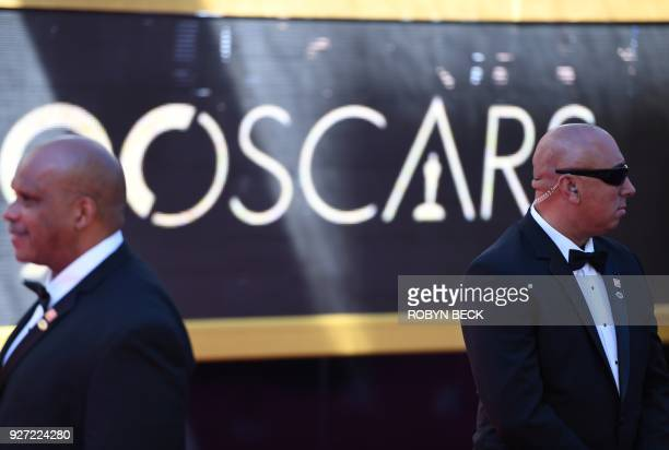 Security members stand guard on the red carpet as guests arrive for the 90th Annual Academy Awards on March 4 in Hollywood California / AFP PHOTO /...
