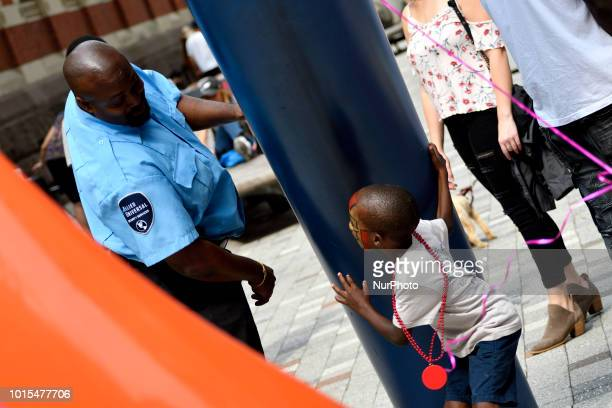 A security officer and a boy play as thousands of pedestrians cyclist skaters joggers participate in the third annual Philly Free Streets event at a...