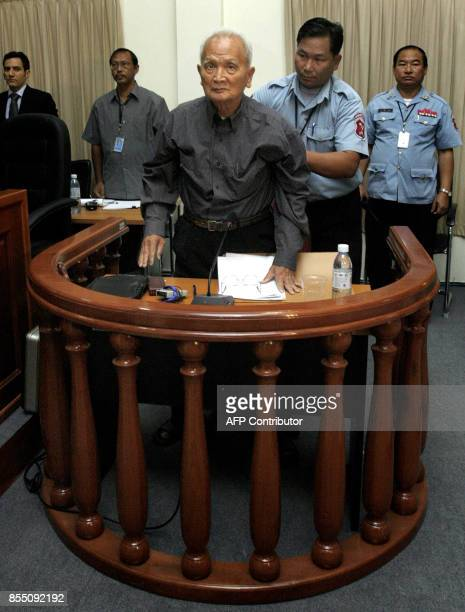 A security officer assists former Khmer Rouge leader Nuon Chea at the tribunal in the Court of Cambodia in Phnom Penh on February 4 2008 Nuon Chea...
