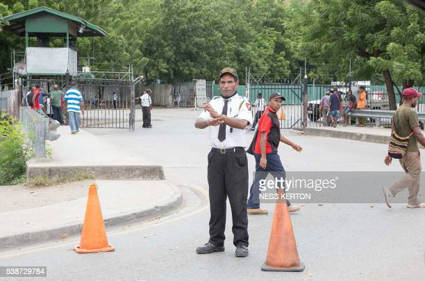 A security officer blocks the main entrance of a major supermarket in Port Moresby following a protest rally by the students in Port Moresby on June...