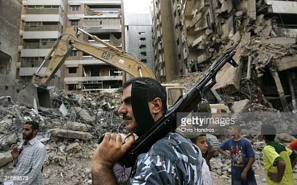 A security officer brandishes an assault rifle while guarding members of Lebanon's government on a tour of Beirut's southern suburbs August 21 2006...
