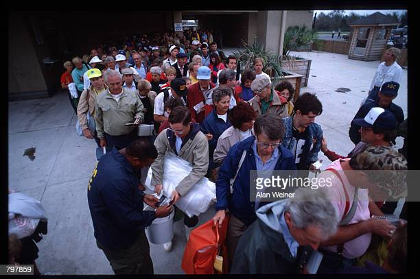A security officer checks a man's ID to verify that he is a resident of the Isle of Palms September 27 1989 in South Carolina Hugo is ranked as the...