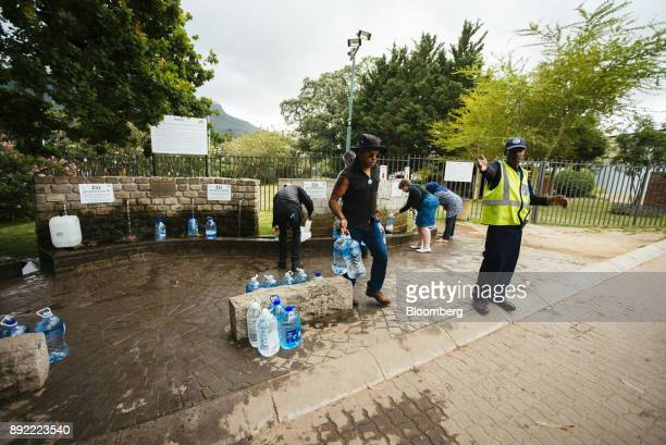 A security officer directs residents as they fill water bottles and containers at the Newlands natural water spring in Cape Town South Africa on...