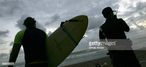 A security officer guards the beach in Seminyak as a surfer walks past on October 4 2005 in Bali Indonesia The Australian government have issued a...