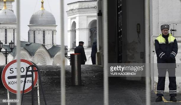 A security officer guards the Kremlin's Spasskaya Tower gate with the domes of the churches and cathedrals inside Moscow's Kremlin seen in the...
