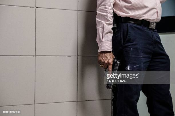 A security officer holds a gun in the building attached to the DusitD2 compound in Nairobi on January 15 after a blast followed by a gun battle...