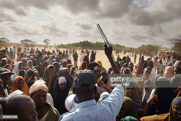 A security officer keeps order for hundreds of people desperate to move to a less crowded refugee camp in Dadaab the world�s biggest refugee complex...