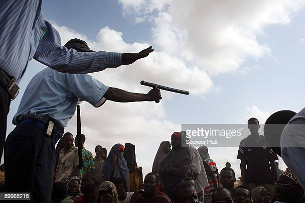 Security officer keeps order for hundreds of people trying to move to a less crowded refugee camp in Dadaab, the world�s biggest refugee complex...